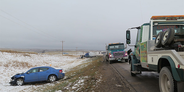 tow trucks recovering a vehicle that slide off a road
